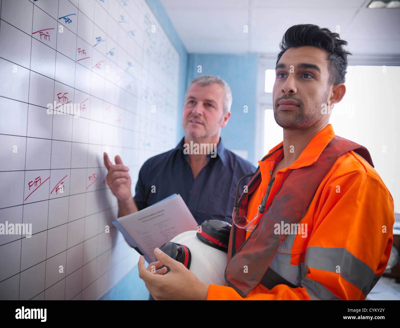 Workers planning operations on board - Stock Image