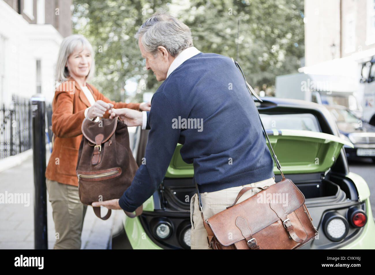 Couple loading car on city street - Stock Image