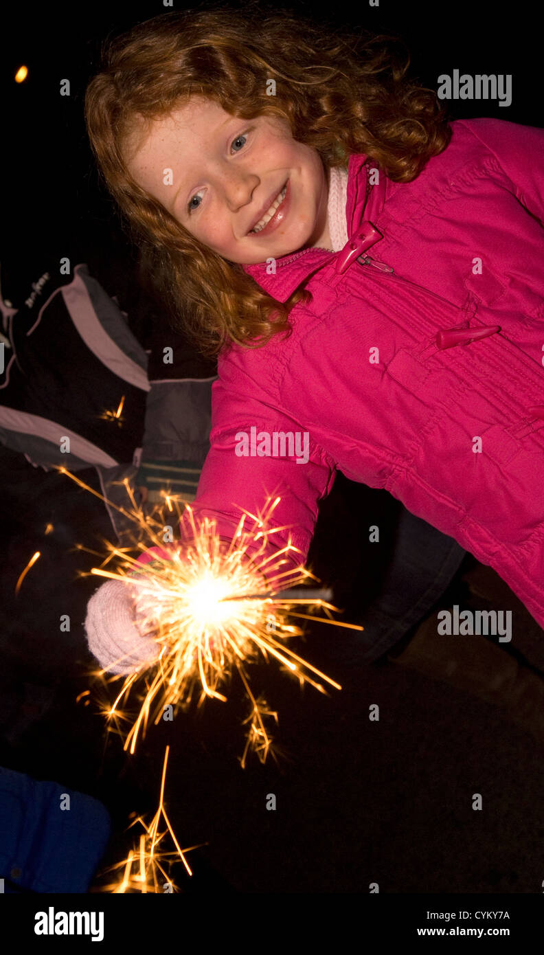6 year old girl having fun with sparklers at firework display, Chiddingfold, Surrey, UK. - Stock Image
