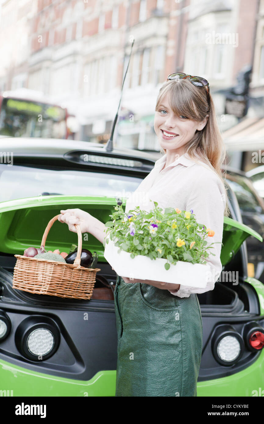 Woman loading produce into car - Stock Image