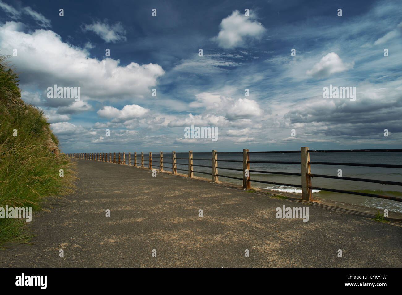 Wooden posts on paved coastal road - Stock Image