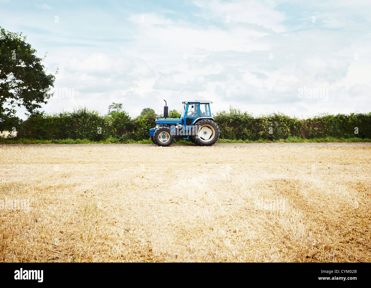 Tractor driving in tilled crop field - Stock Image