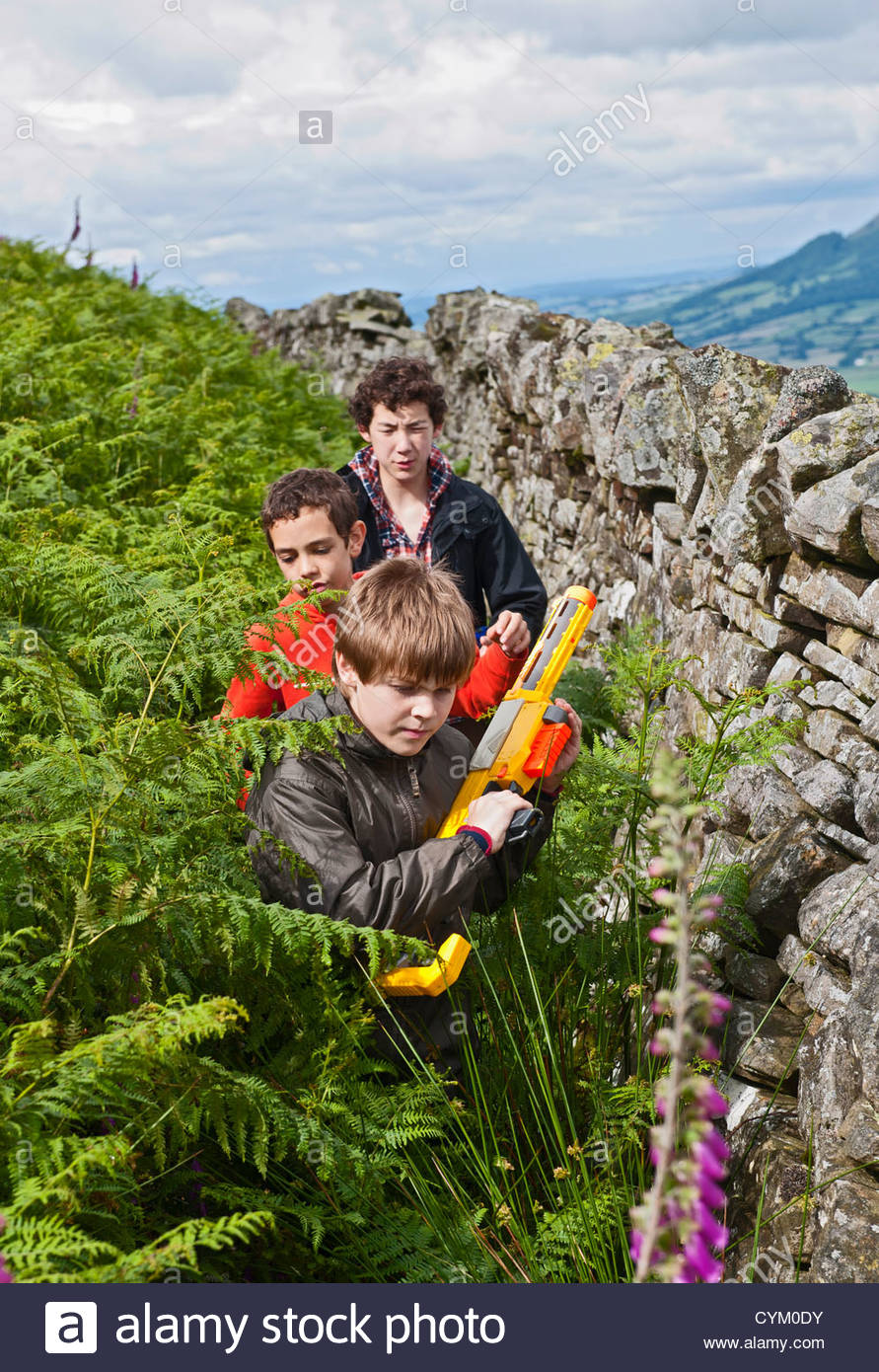 Boys playing with squirt guns outdoors - Stock Image