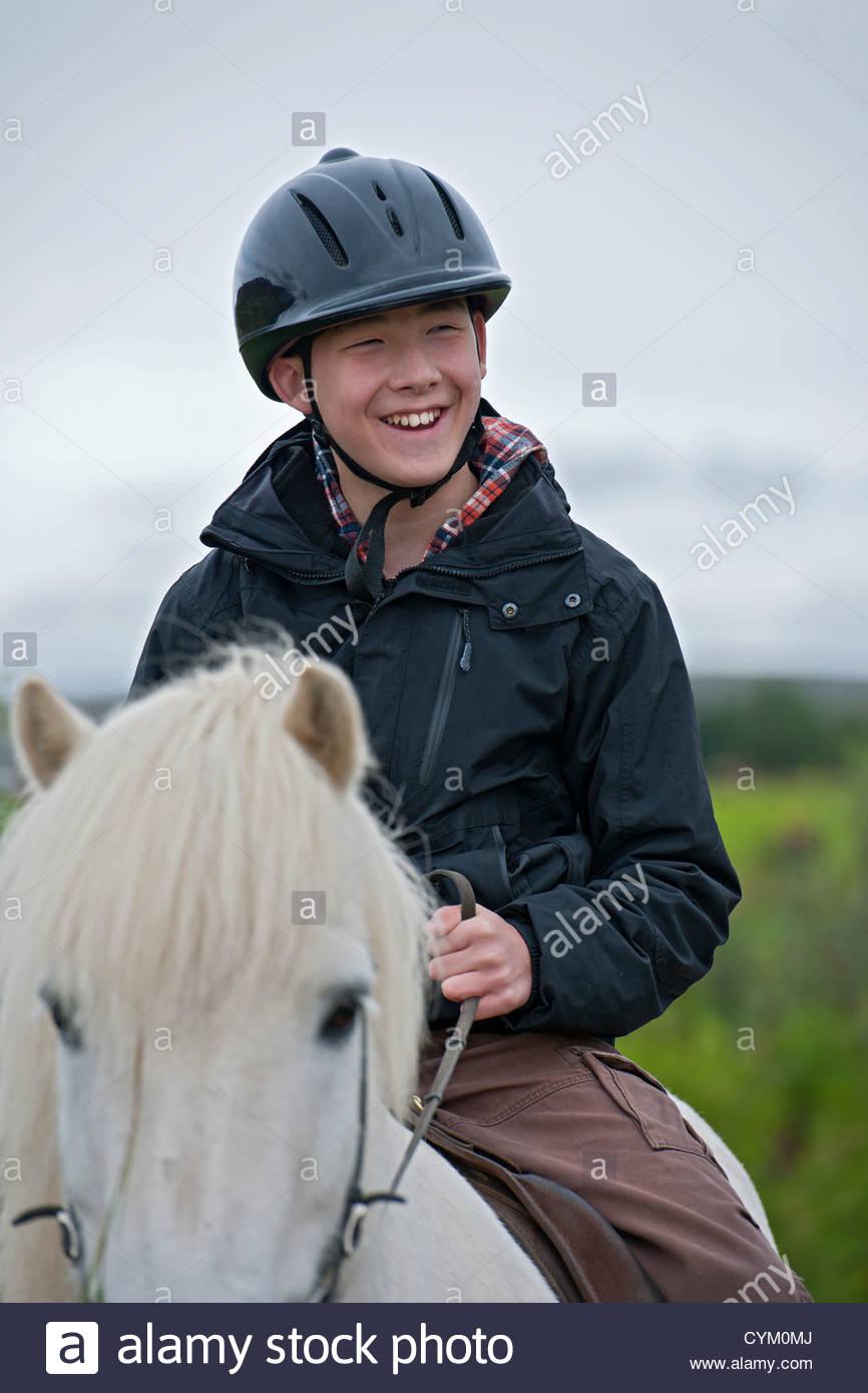 Smiling boy riding horse outdoors - Stock Image