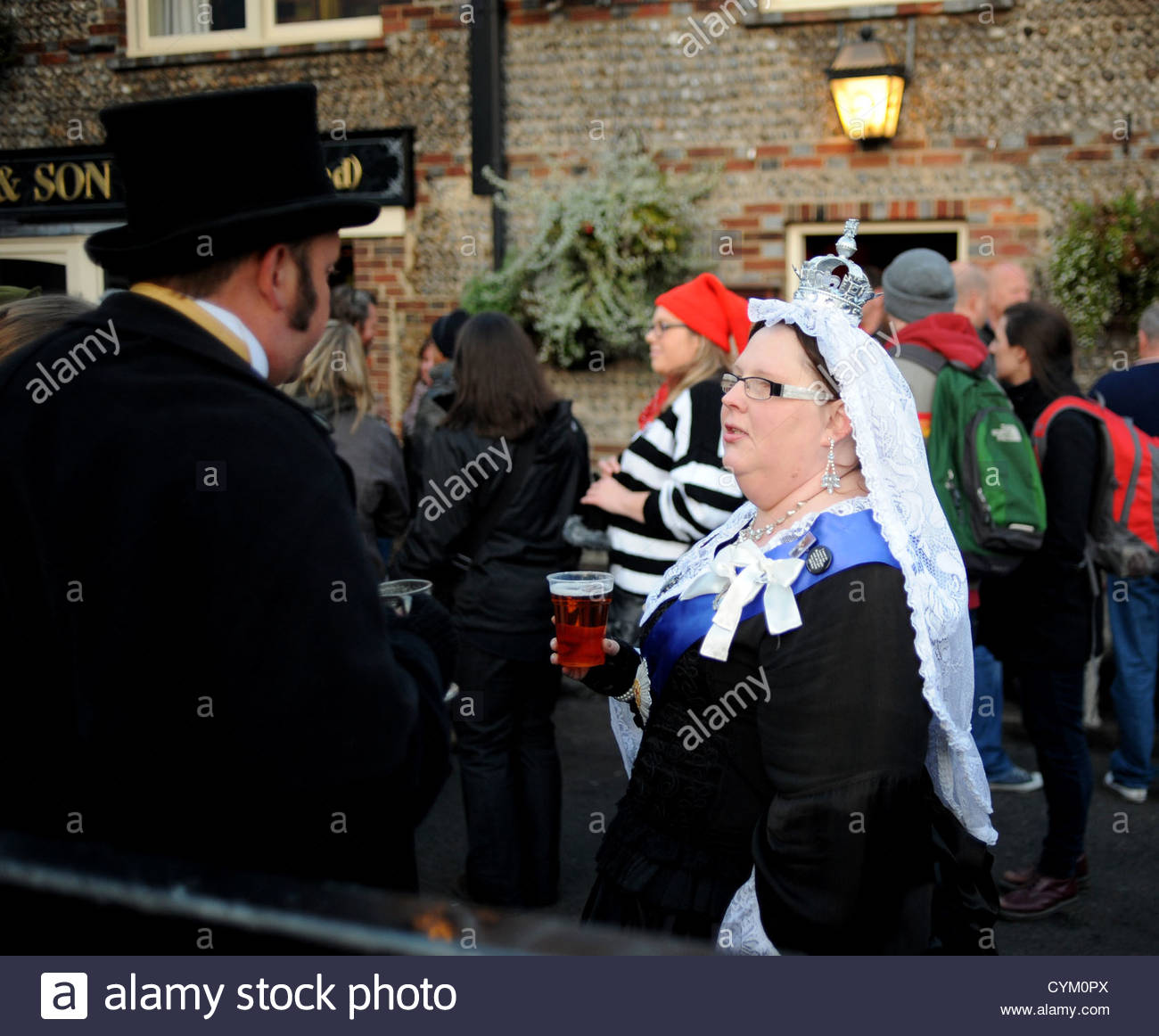 Woman dressed as Queen Victoria drinking pint of beer at Lewes Bonfire Celebrations 2012 - Stock Image