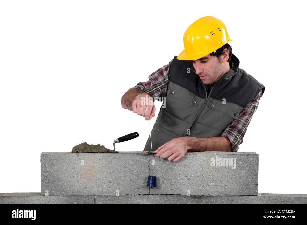 Tradesman using a plumb-bob Stock Photo