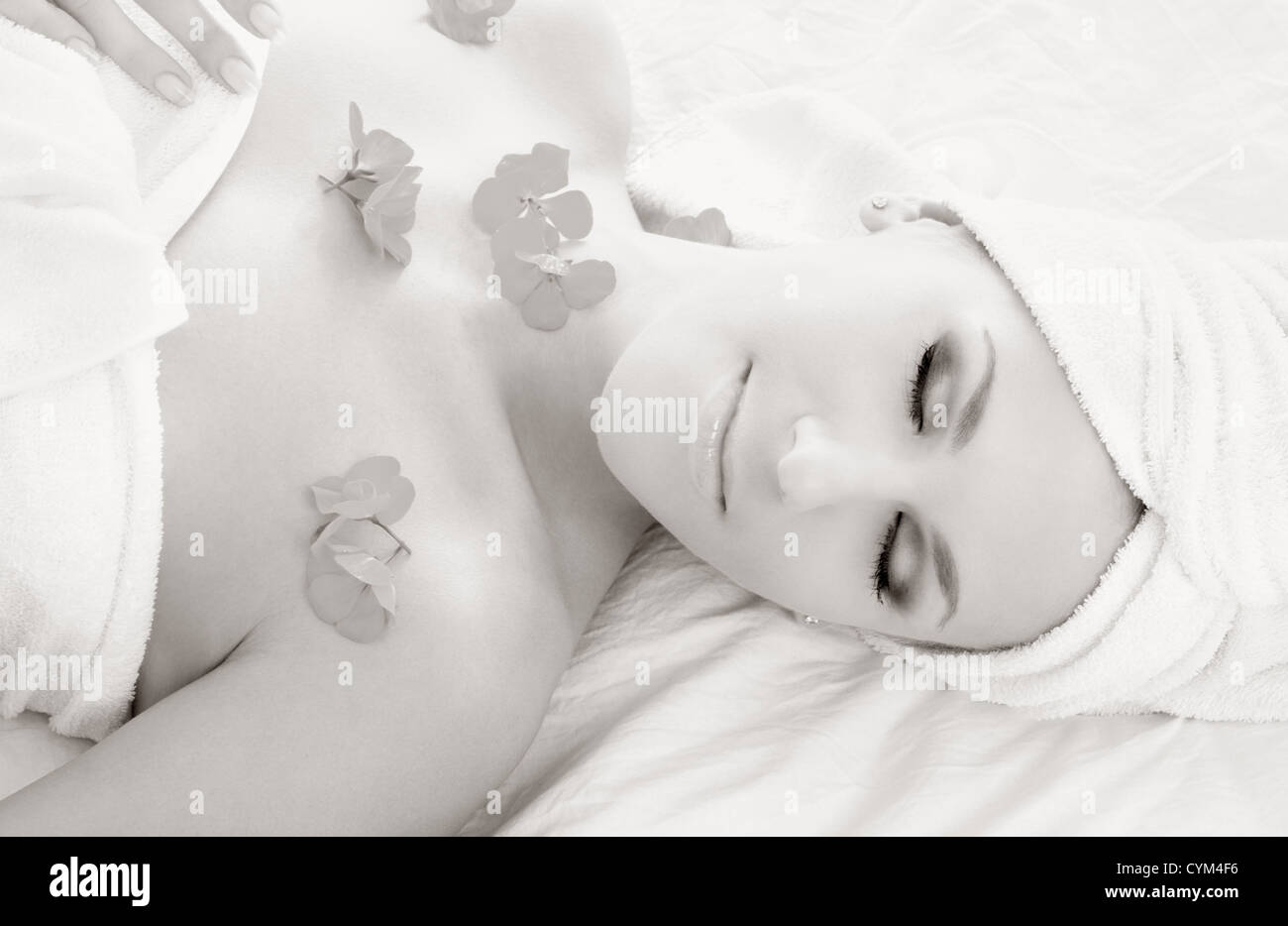 monochrome picture of beautiful lady with flowers in spa - Stock Image