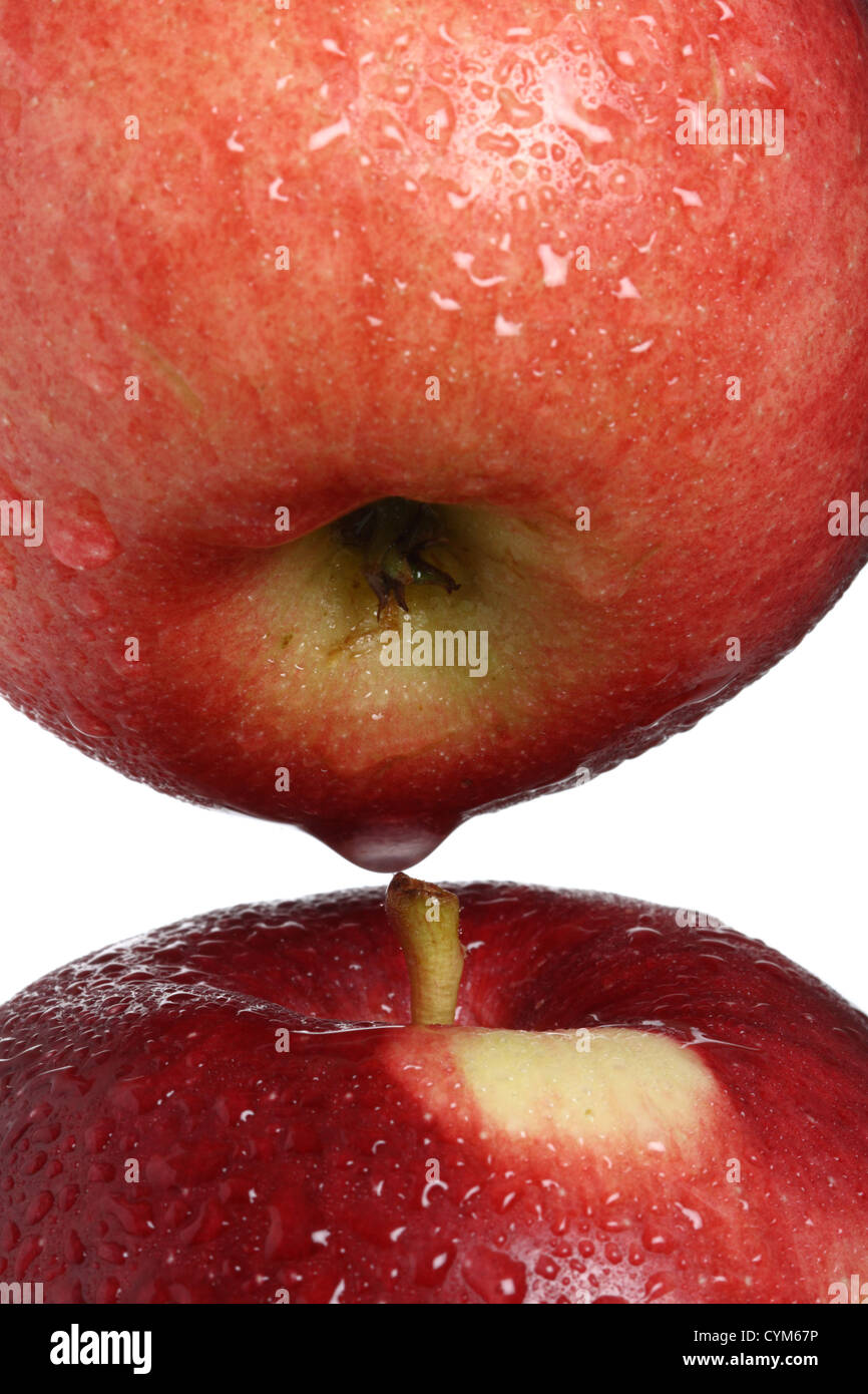 two red apples with drops of water free-standing, soft focus on cores - Stock Image