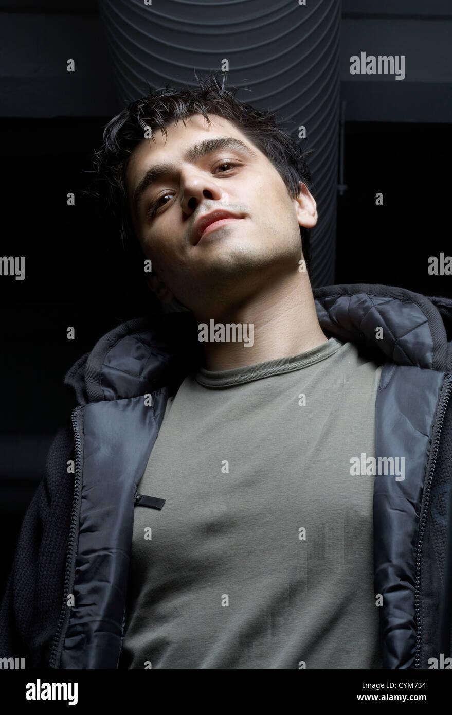 dark portrait of street mobster in industrial building basement - Stock Image