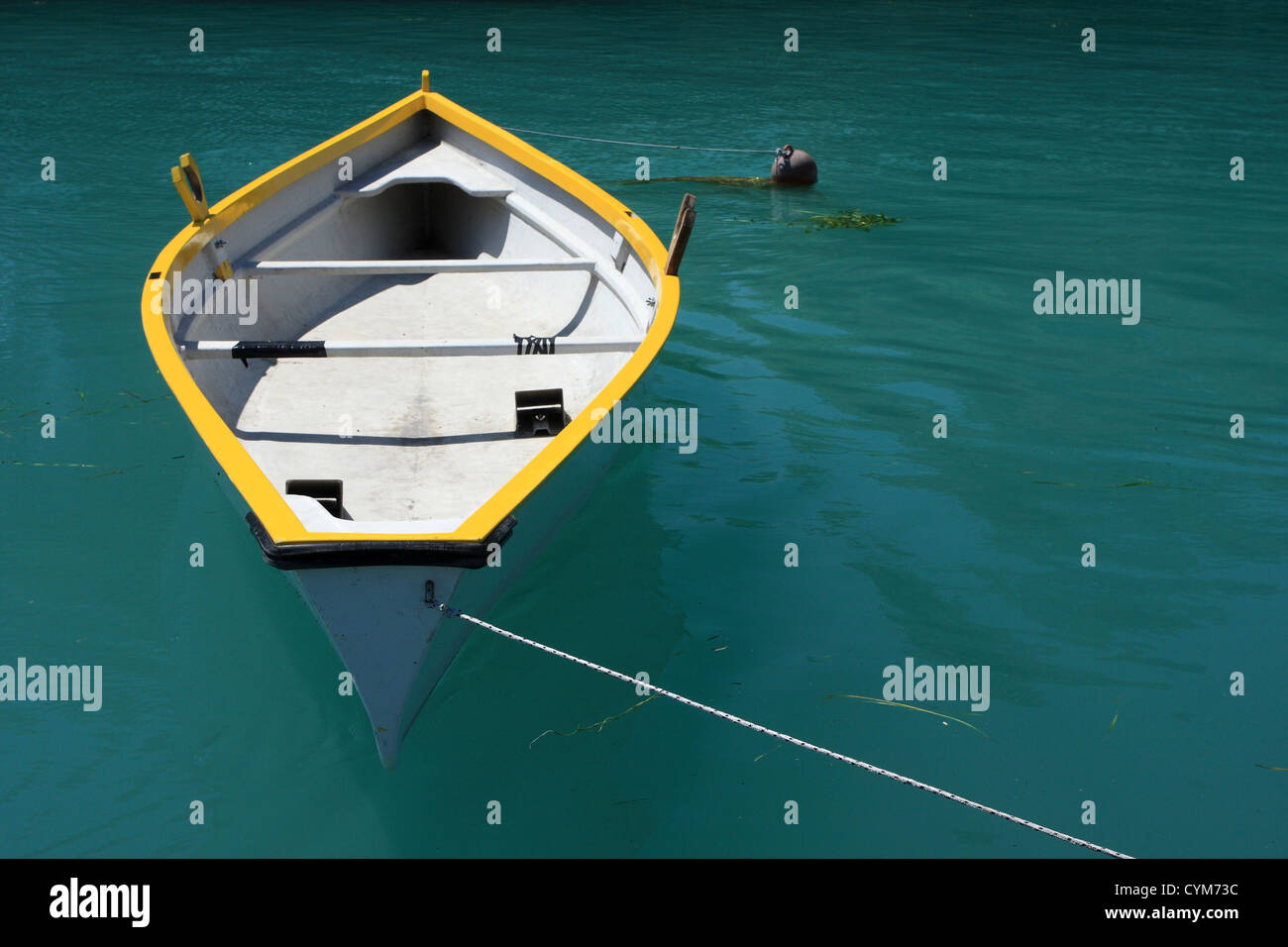 A yellow and white rowing boat on deep green water, plenty of copy space - Stock Image