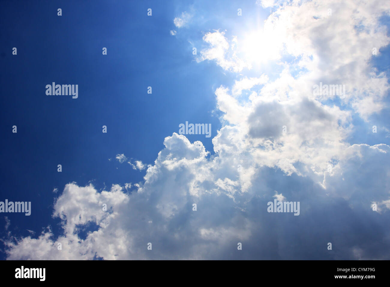 clouds on a blue sky, sun shines strongly behind some clouds, good copy space to the left - Stock Image