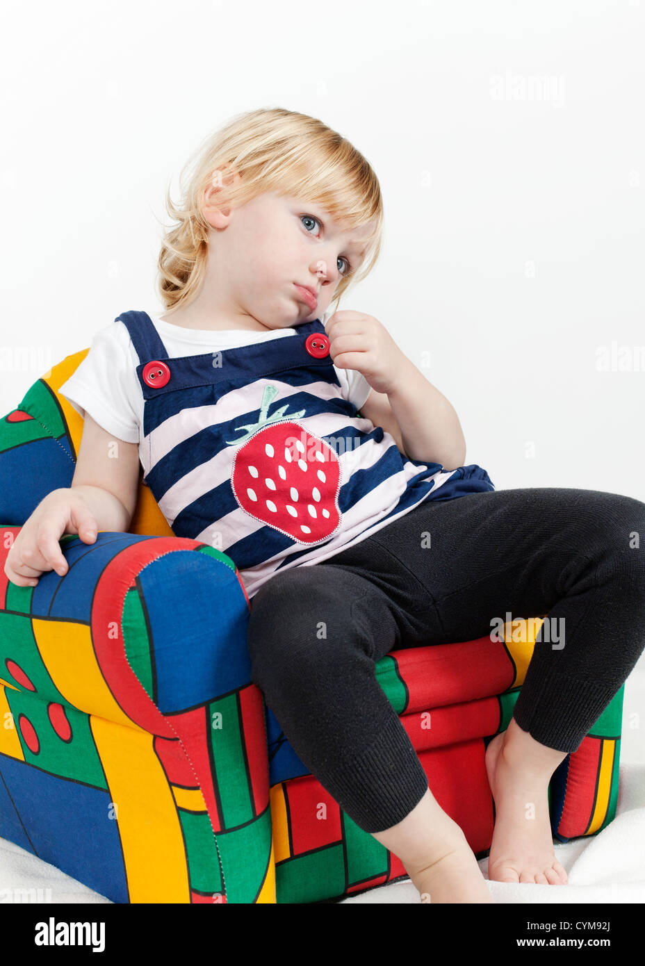 Little girl in a colorful armchair - Stock Image