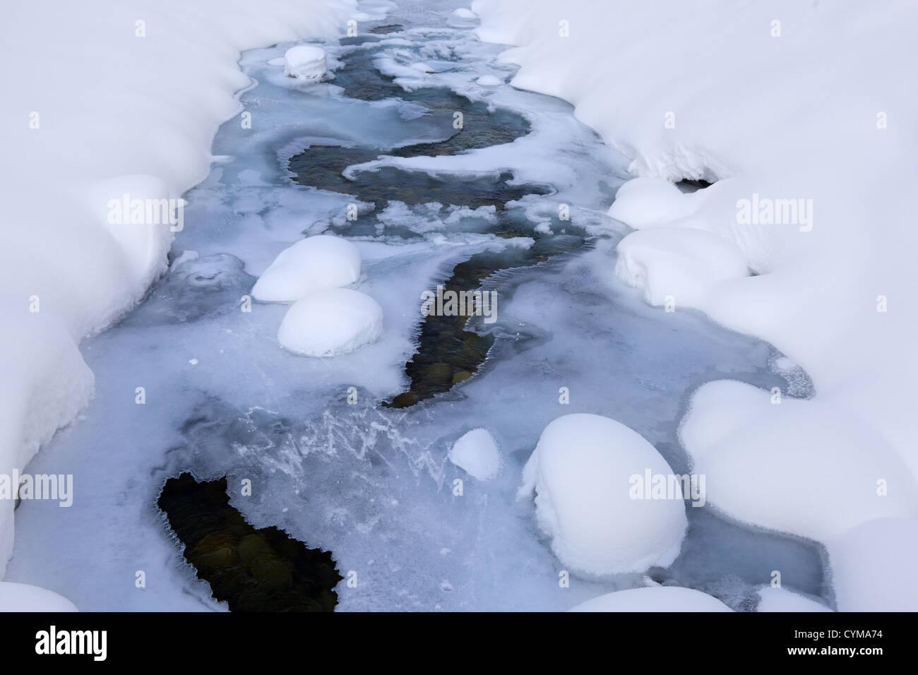 La Navisence, a snowy glacial river partly frozen - Stock Image