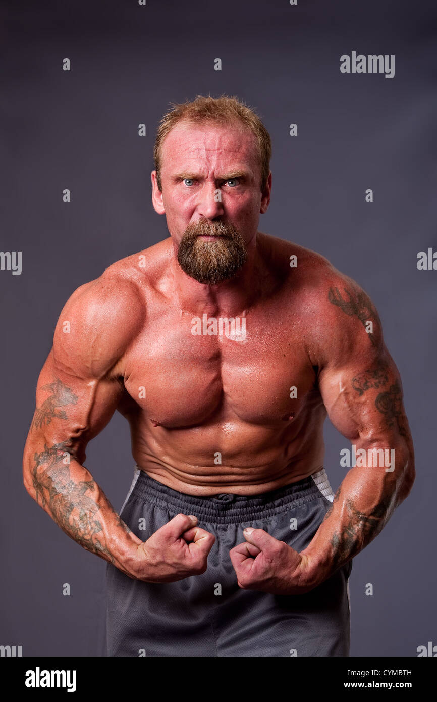 Middle aged Caucasian body builder man flexing muscles showing torso pecs, biceps and veins, isolated. - Stock Image