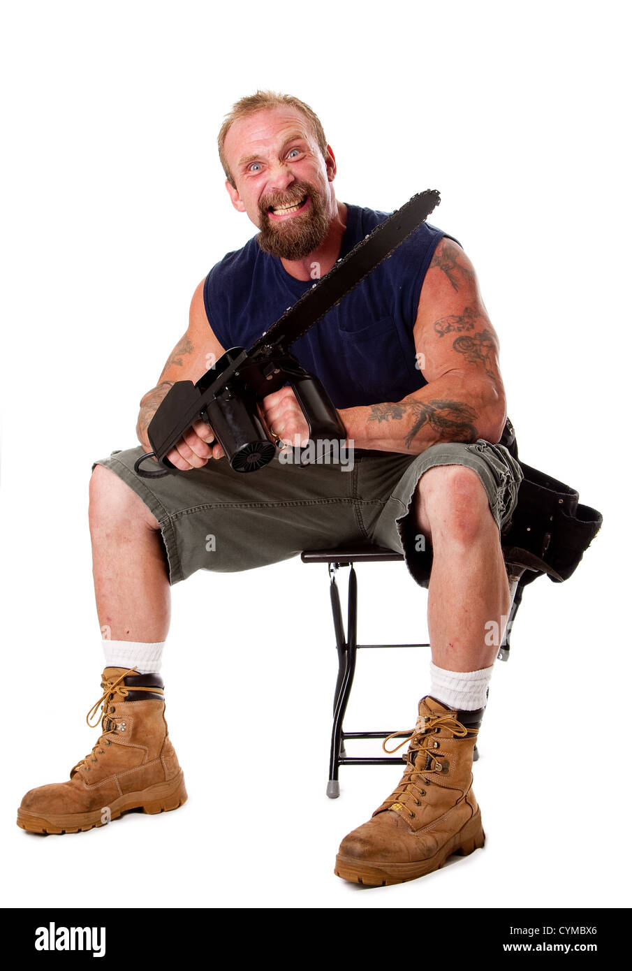 Crazy Caucasian man with tattoos and chainsaw sitting on stool with strong facial expression, isolated. Stock Photo