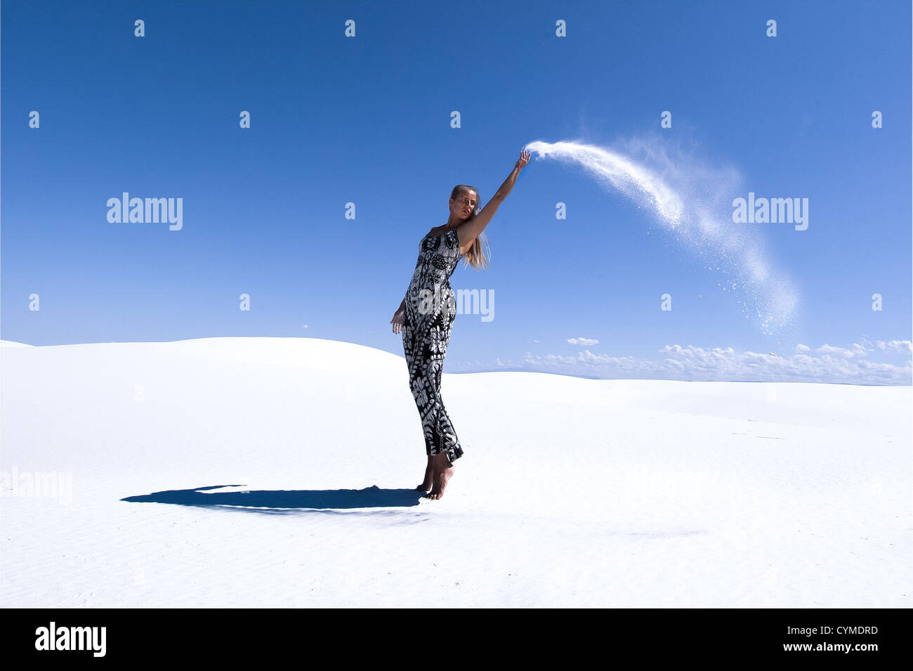 Girl throwing sand in White Sands, New Mexico - Stock Image
