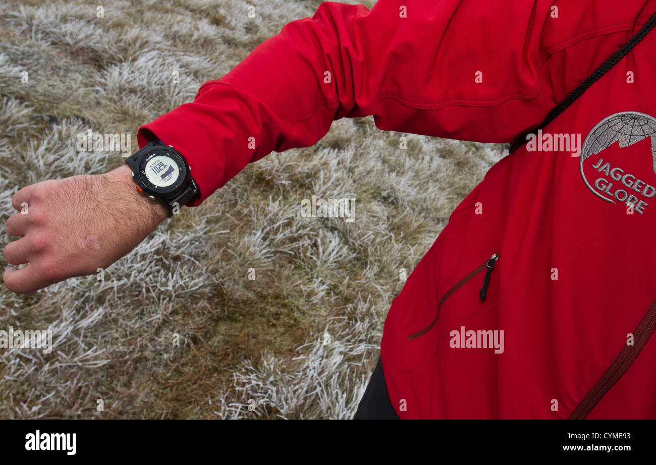 A man using a wrist watch GPS navigation system in the Scottish Mountains - Stock Image