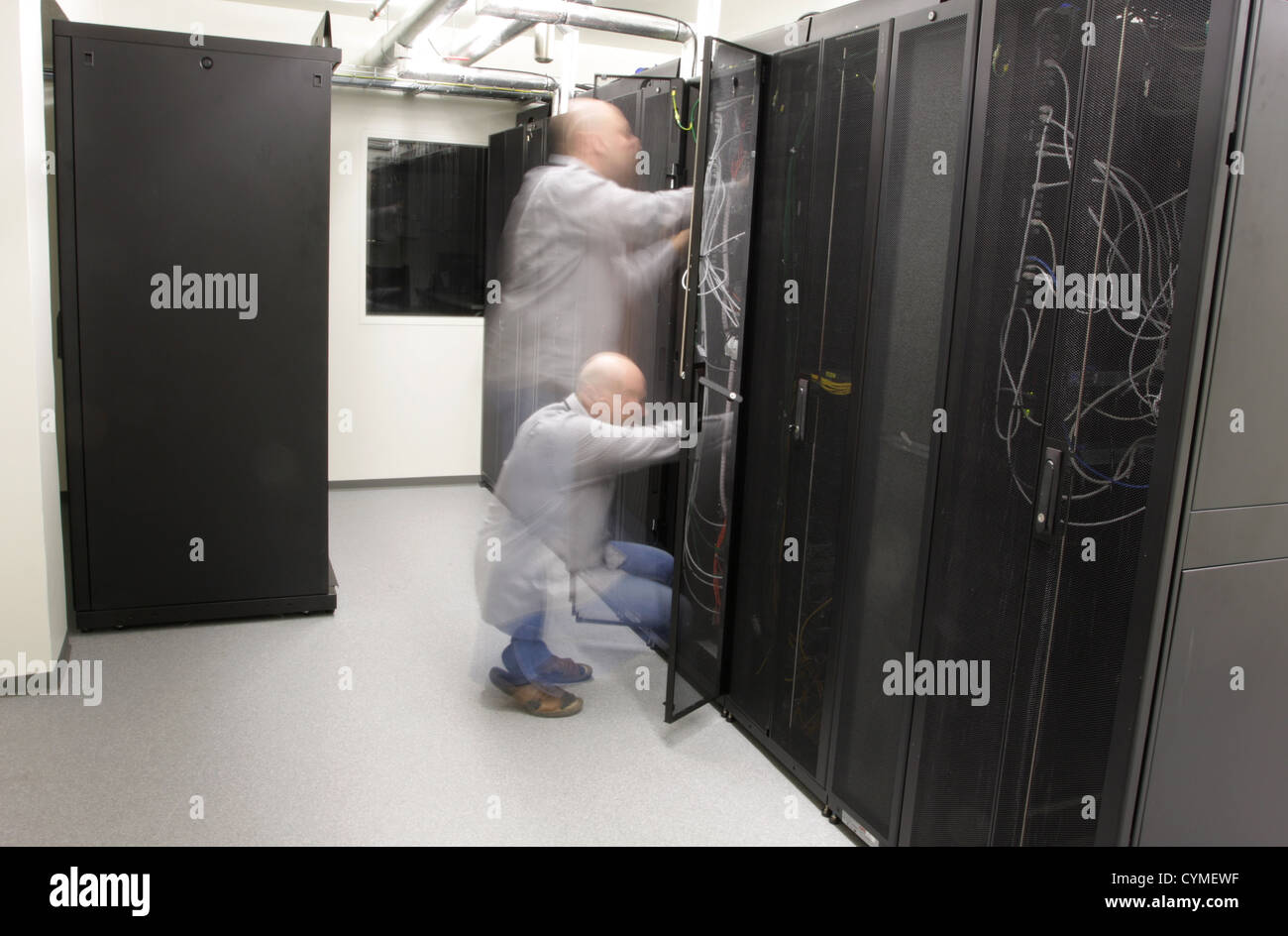 Network technician doing preventive work on a network, long exposure blurres person - Stock Image