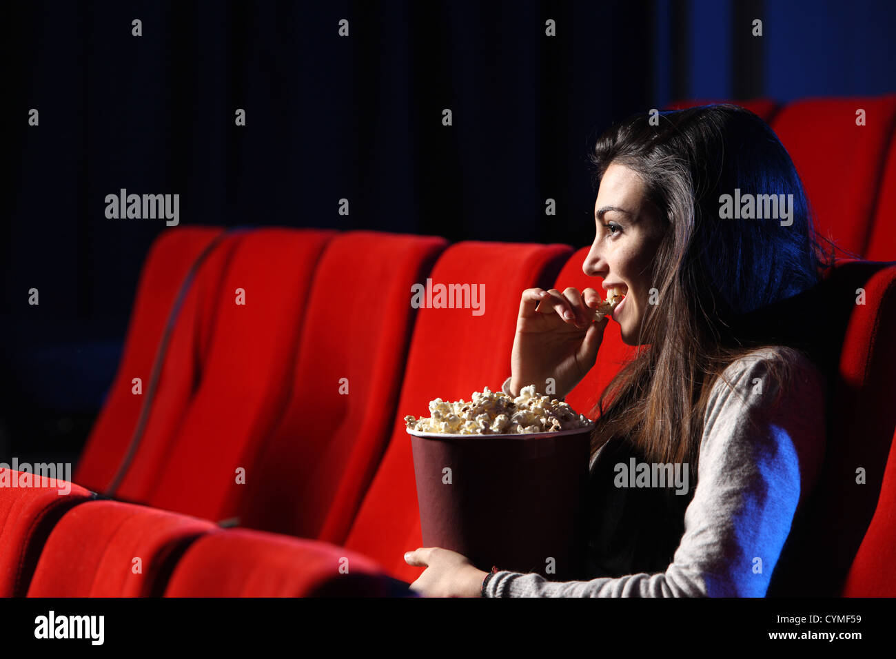 portrait of a pretty young woman, she  eats popcorn and smiles - Stock Image
