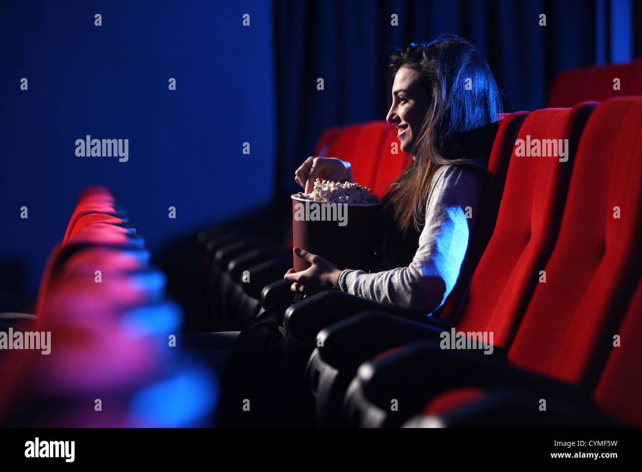 funny movie: portrait of a pretty young woman, eats popcorn and smiles, side view - Stock Image