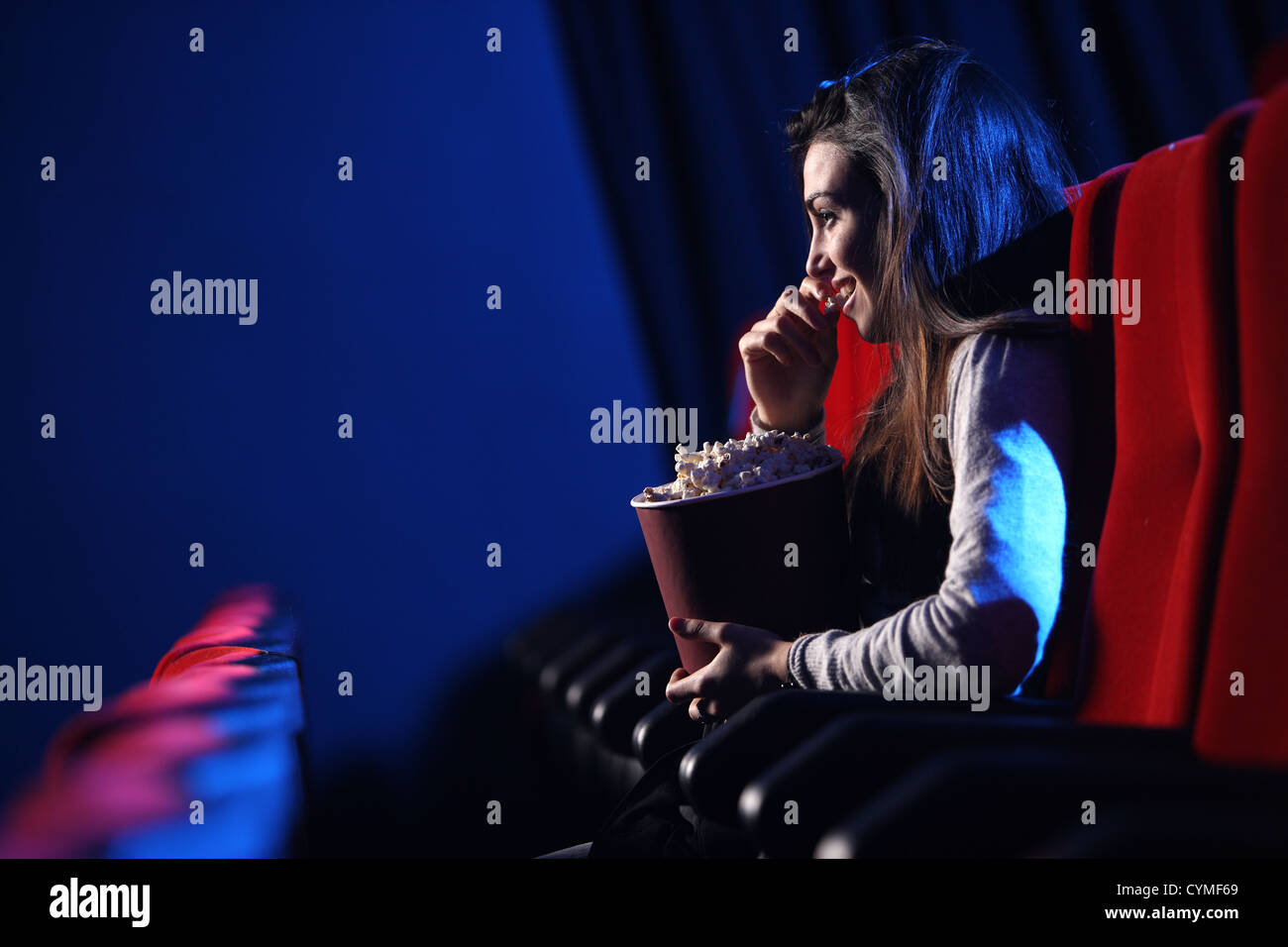 funny movie: portrait of a pretty young woman, she  eats popcorn and smiles - Stock Image