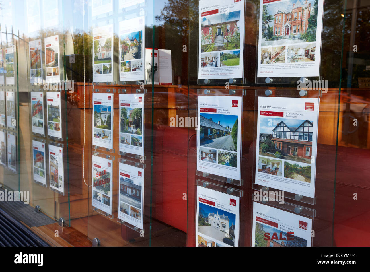 properties for sale in an estate agent window in central dublin republic of ireland - Stock Image