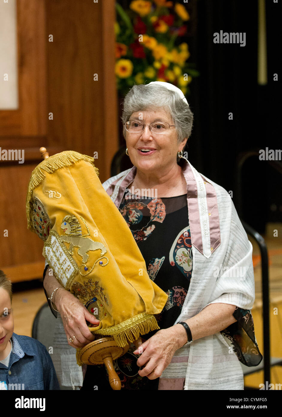 Jewish woman, 67, holds Torah during her Bat Mitzvah ceremony during Sabbath service at her synagogue - Stock Image