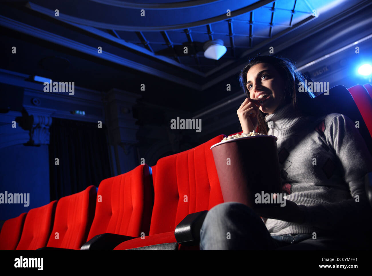 a pretty young woman sitting in an empty theater, she eats popcorn and smiles - Stock Image