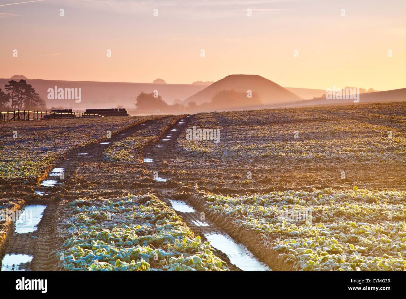 Frosty autumnal sunrise over Wiltshire countryside landscape with iconic neolithic Silbury Hill in the distance - Stock Image