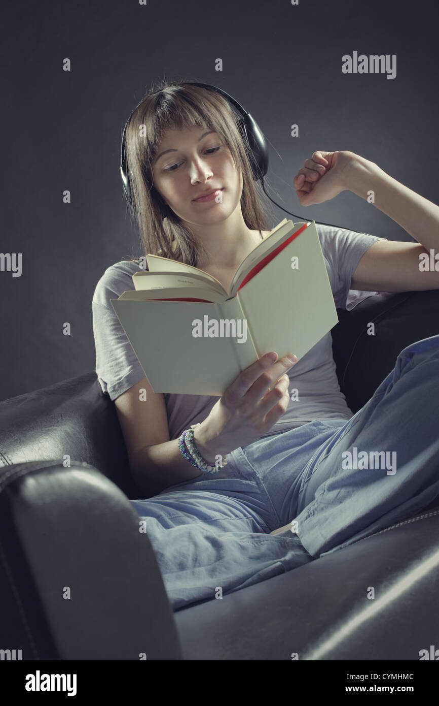 A young woman sits on a couch  reading a book and listening to music through a pair of headphones - Stock Image
