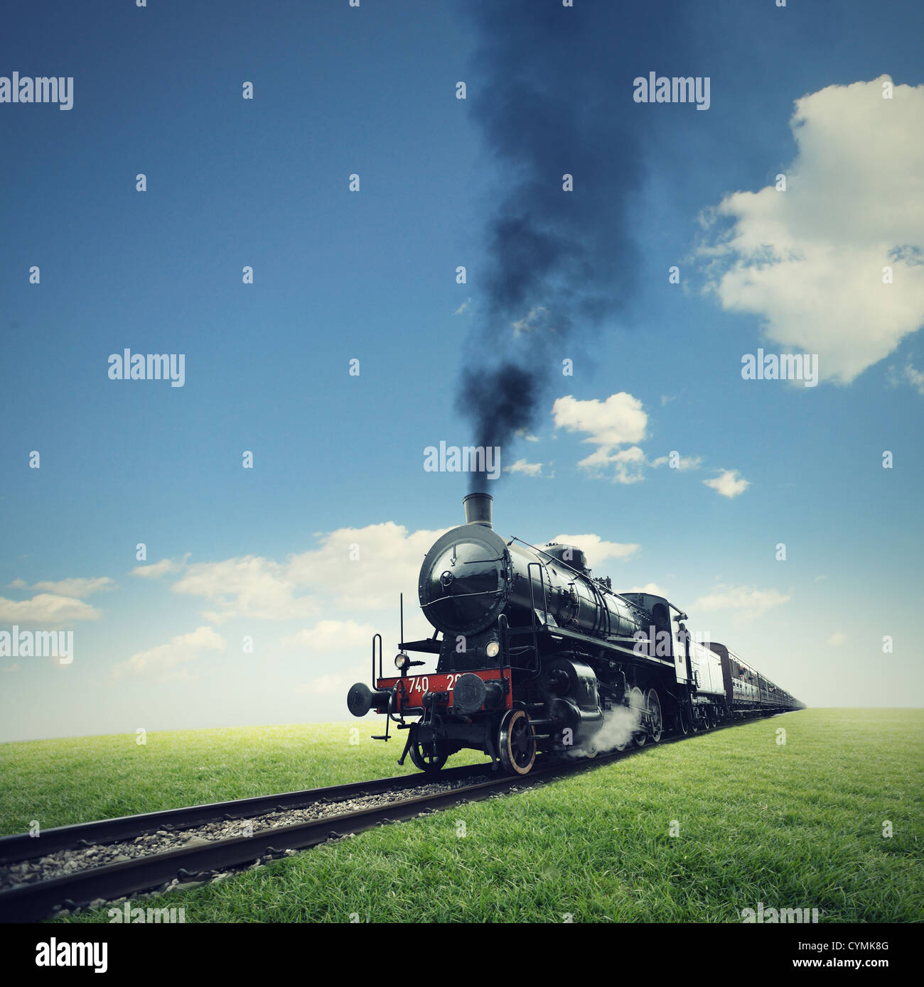 steam engine train crosses a green lawn - Stock Image