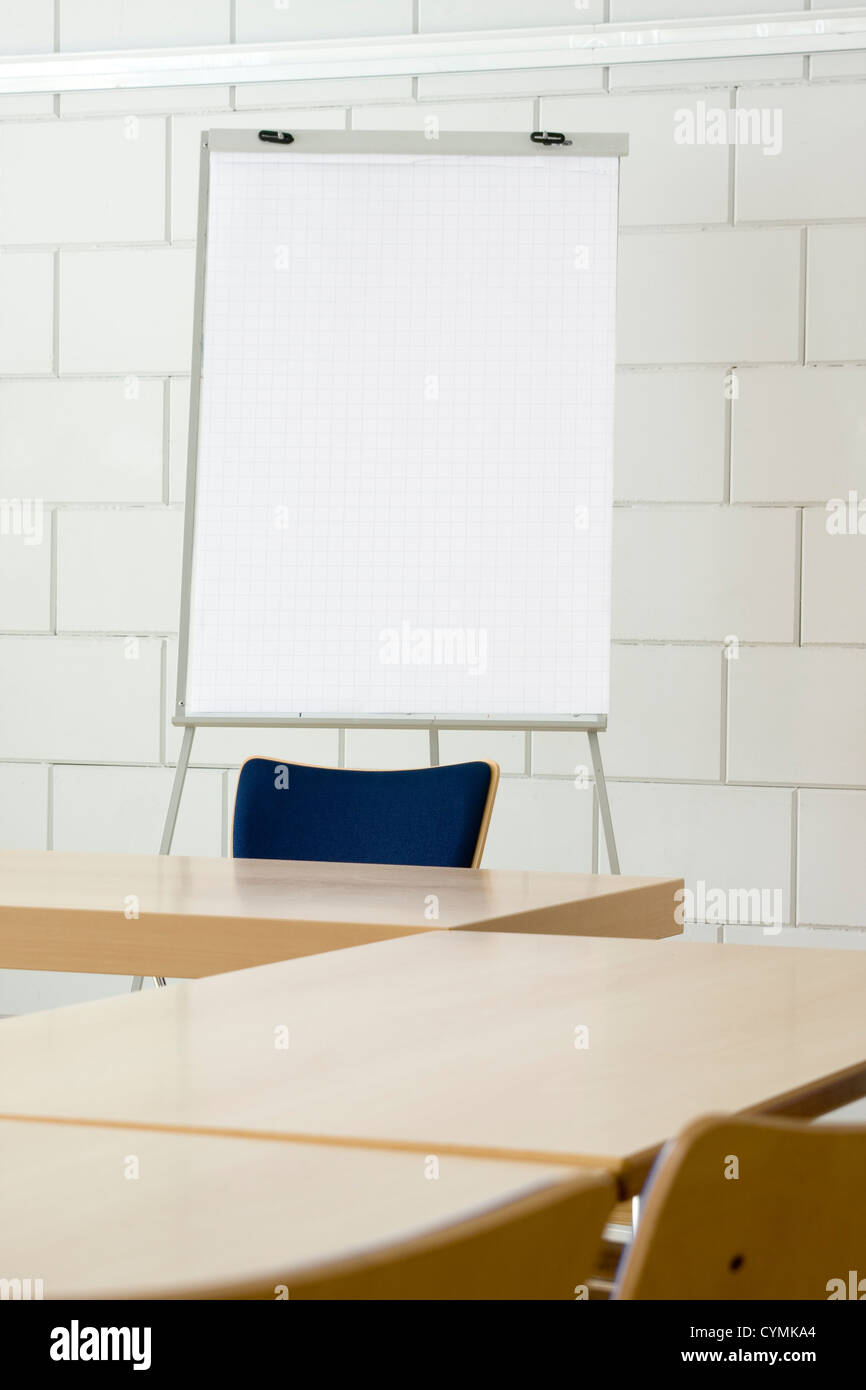 White empty billboard in a meeting room with tables and chairs - Stock Image