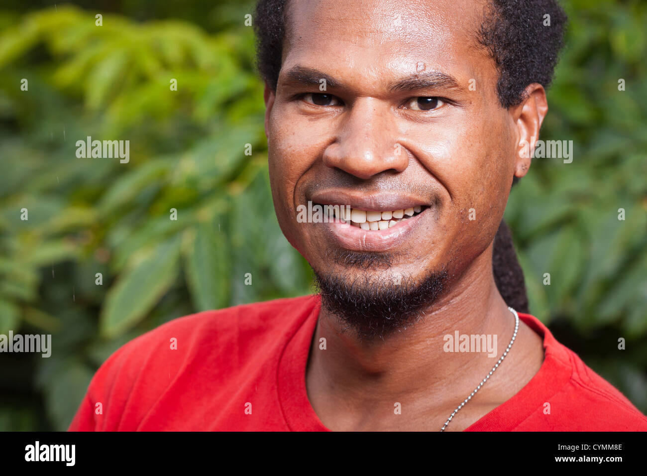 Close-up portrait of a dark skinned smiling young man - Stock Image