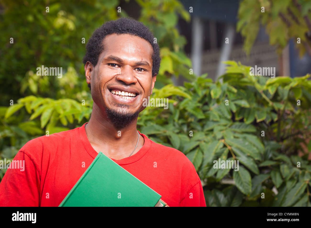A happy dark skinned malel student - Stock Image
