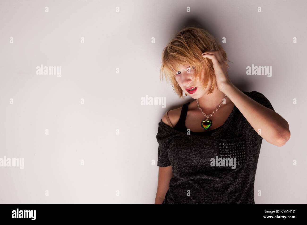 Apprehensive Teenage Girl Standing Against a White Wall - Stock Image