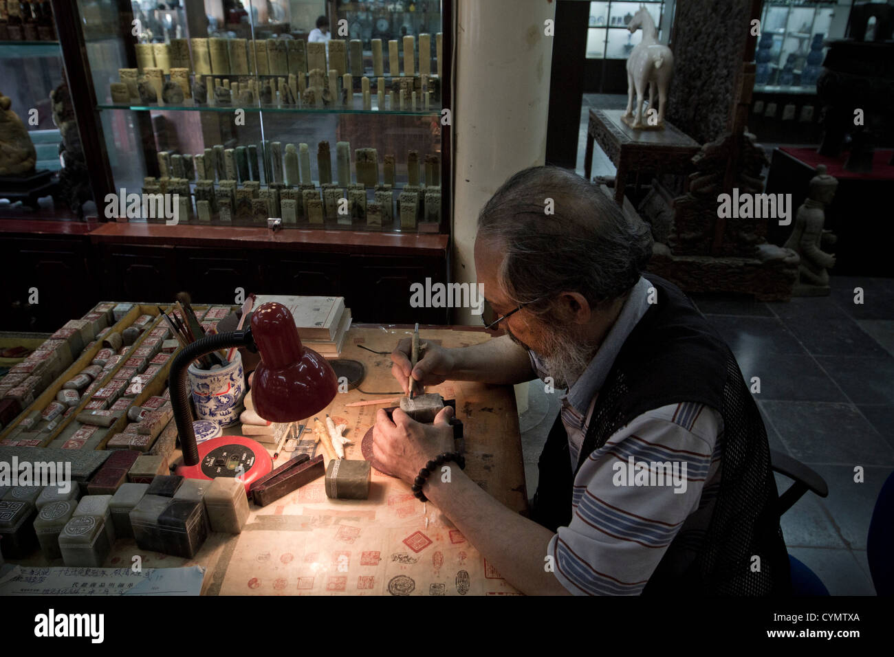 An engraver at work in a shop in a street in Liulichang, Beiijing China. - Stock Image