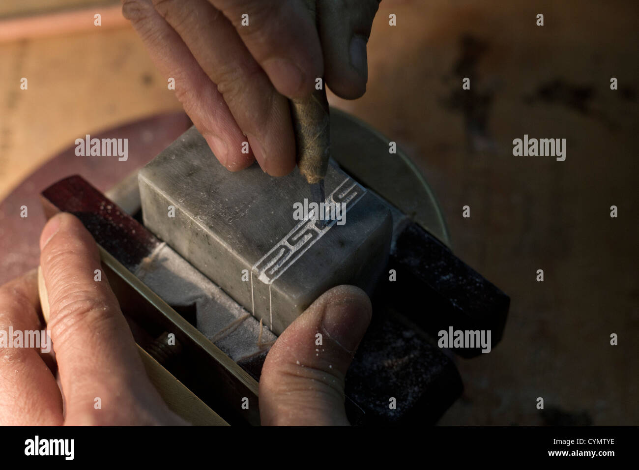 An engraver at work in a shop in a street in Liulichang, Beijing China. - Stock Image