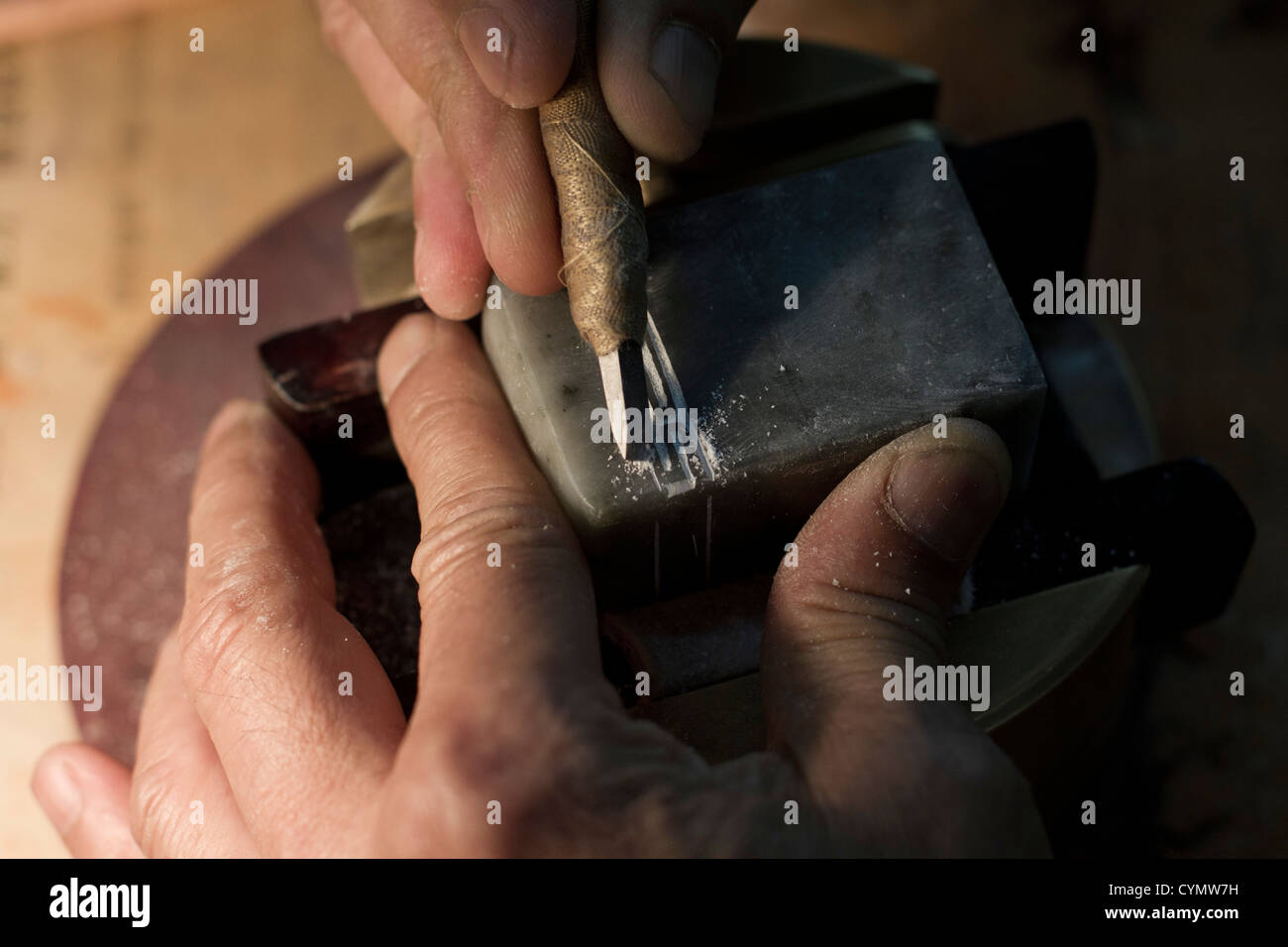 An engraver at work in a shop in a street in Liulichang Beijing China. - Stock Image