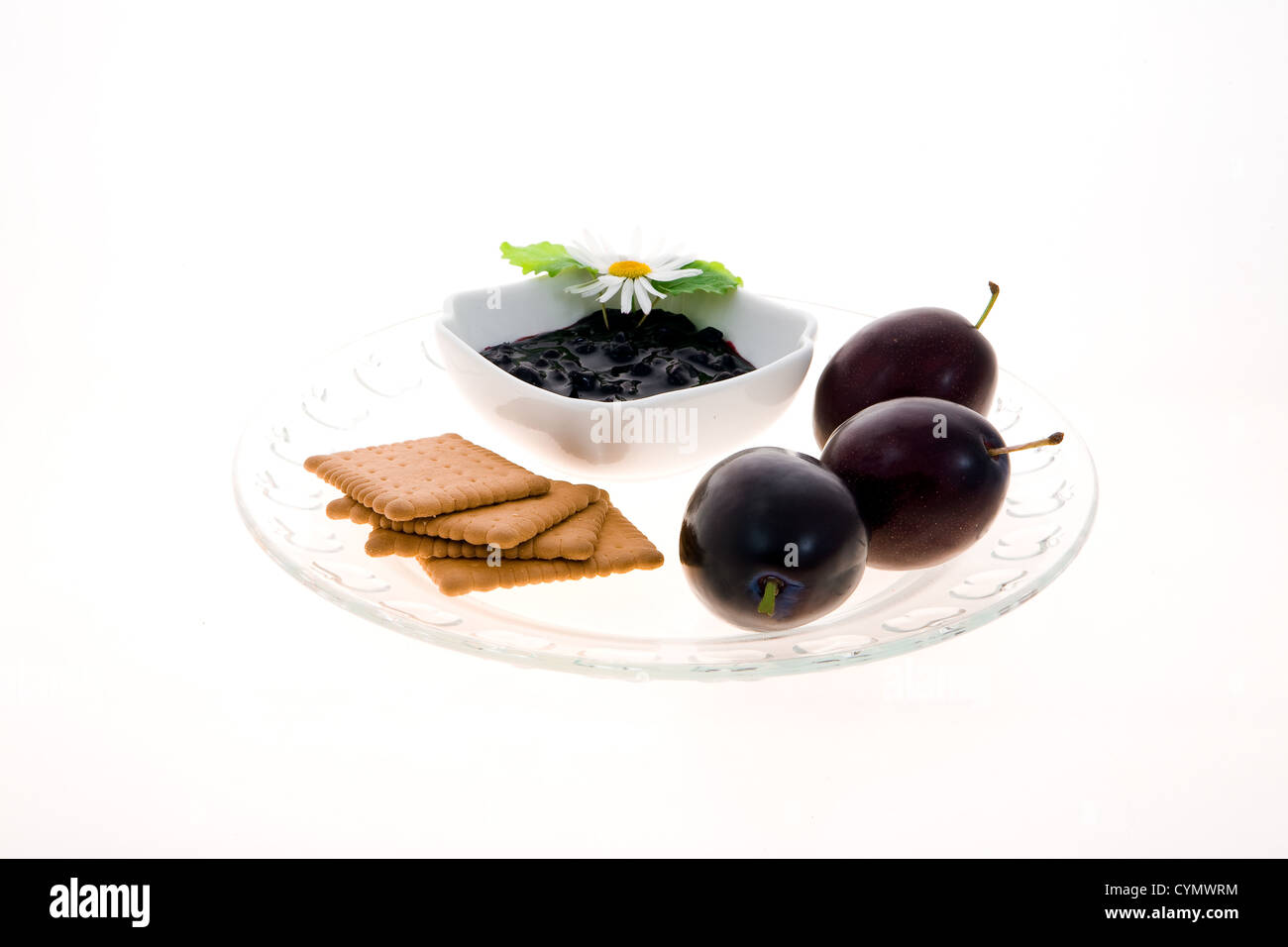 Composition of plums, plum confiture with white flower and biscuits - Stock Image