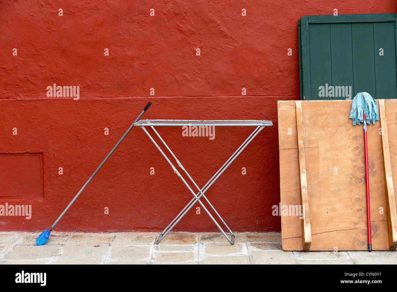 Ironing board and mops drying in the street outside a house newly painted rust-red, in Burano, Venice - Stock Image