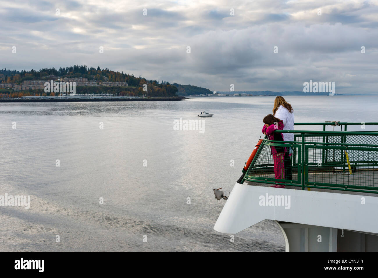 Mother and daughter on deck of Washington State Ferry between Edmonds and Kingston looking back towards Edmonds, - Stock Image