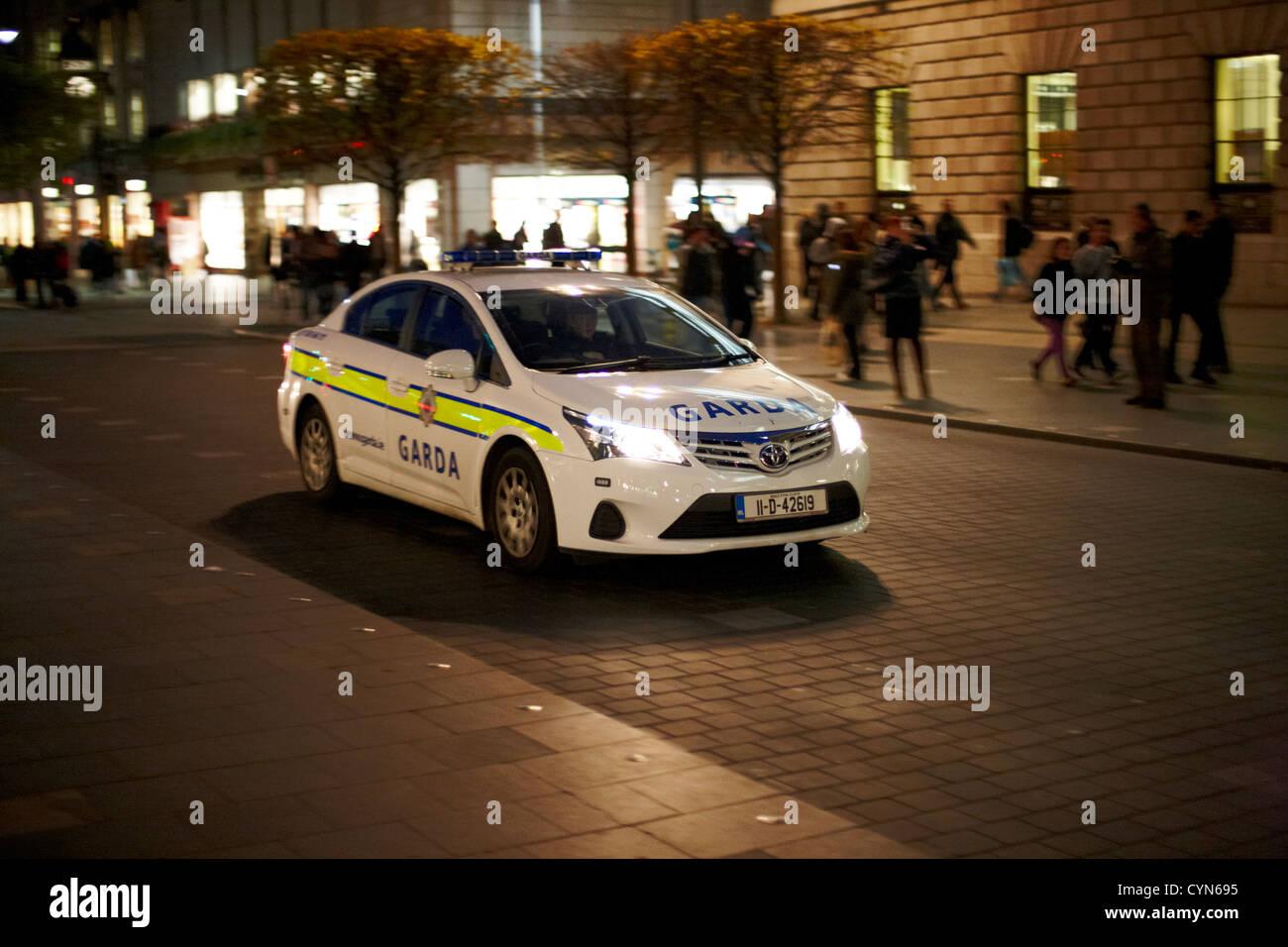 garda siochana patrol car driving along oconnell street at night dublin republic of ireland Stock Photo