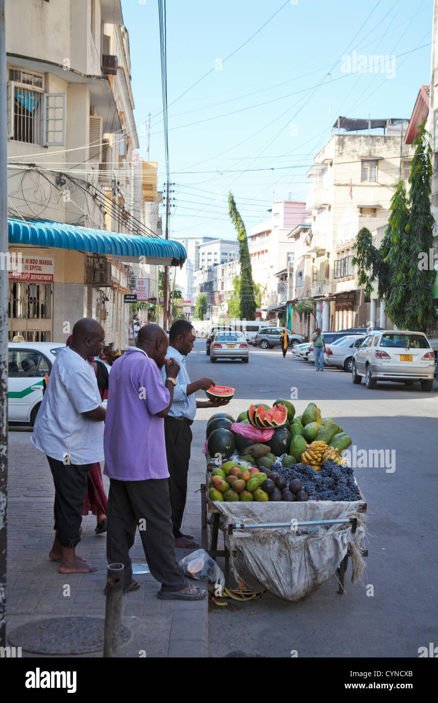 Men eating fruit in street, Dar Es Salaam, Tanzania - Stock Image