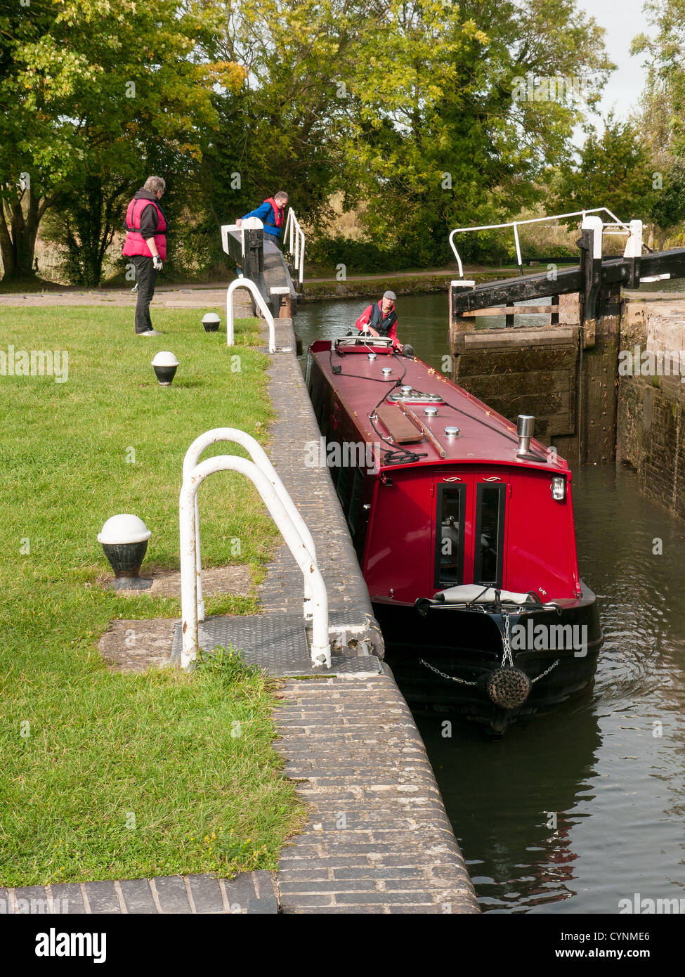 Red Narrow boat and lock keeper on the Grand Union Canal at Marsworth, Buckinghamshire, UK Stock Photo