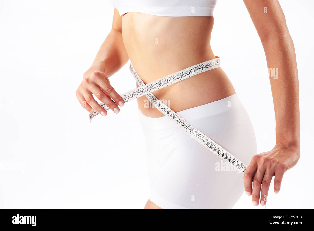 woman measuring her abdomen with a meter-stick - Stock Image