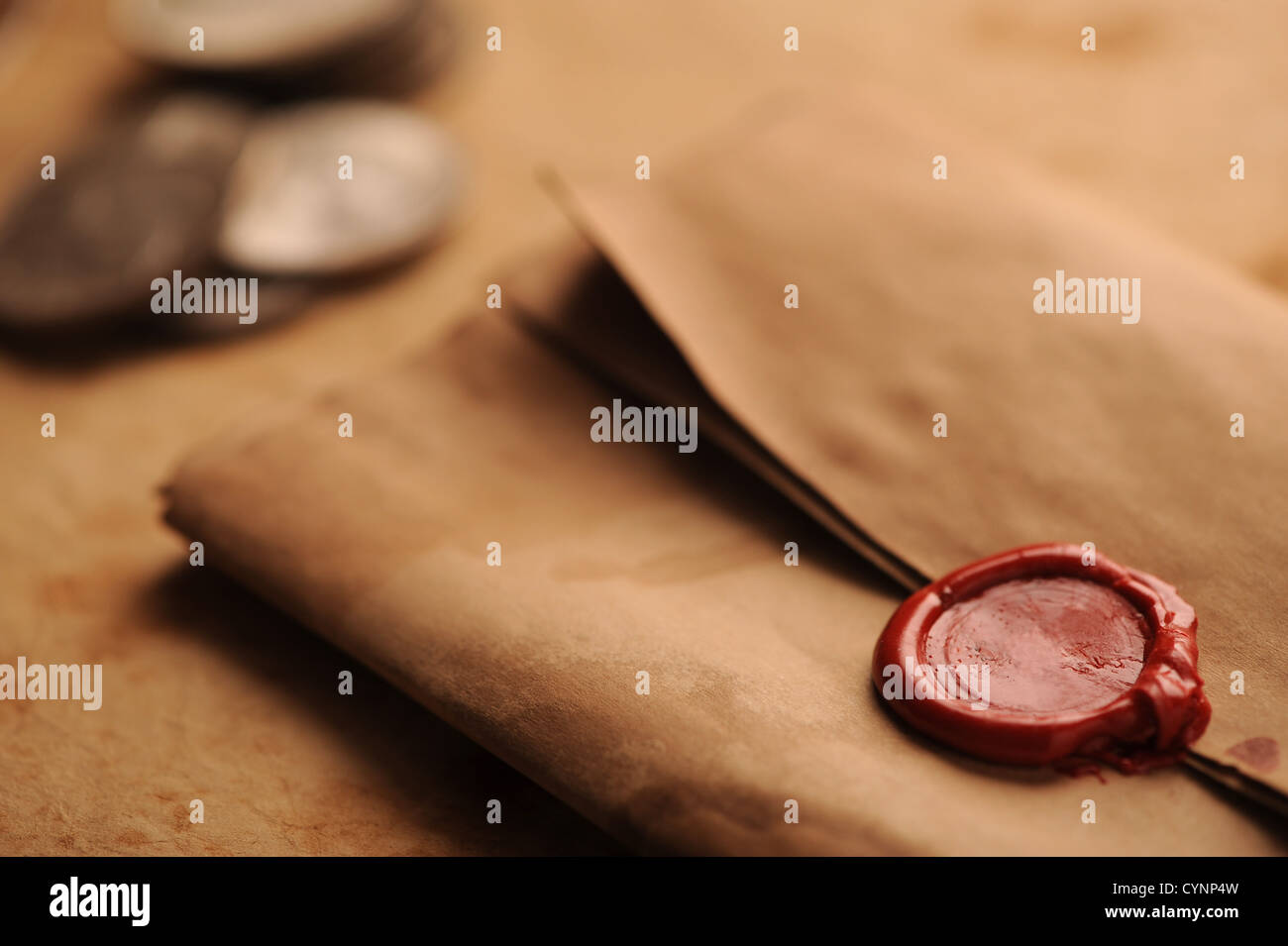 wax seal on a grunge paper, old coins on background - Stock Image