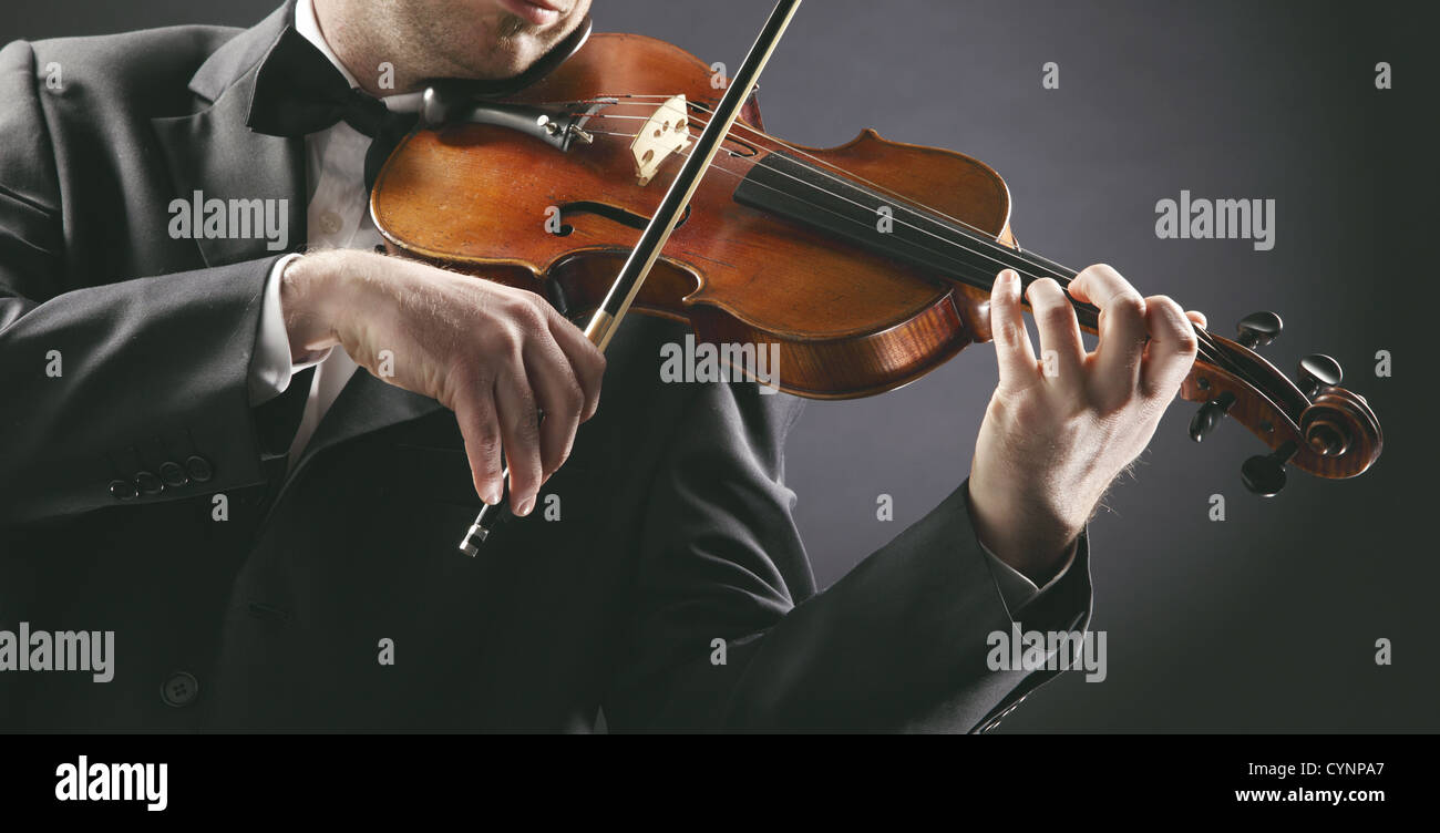 the violinist: Musician playing violin on dark background - Stock Image