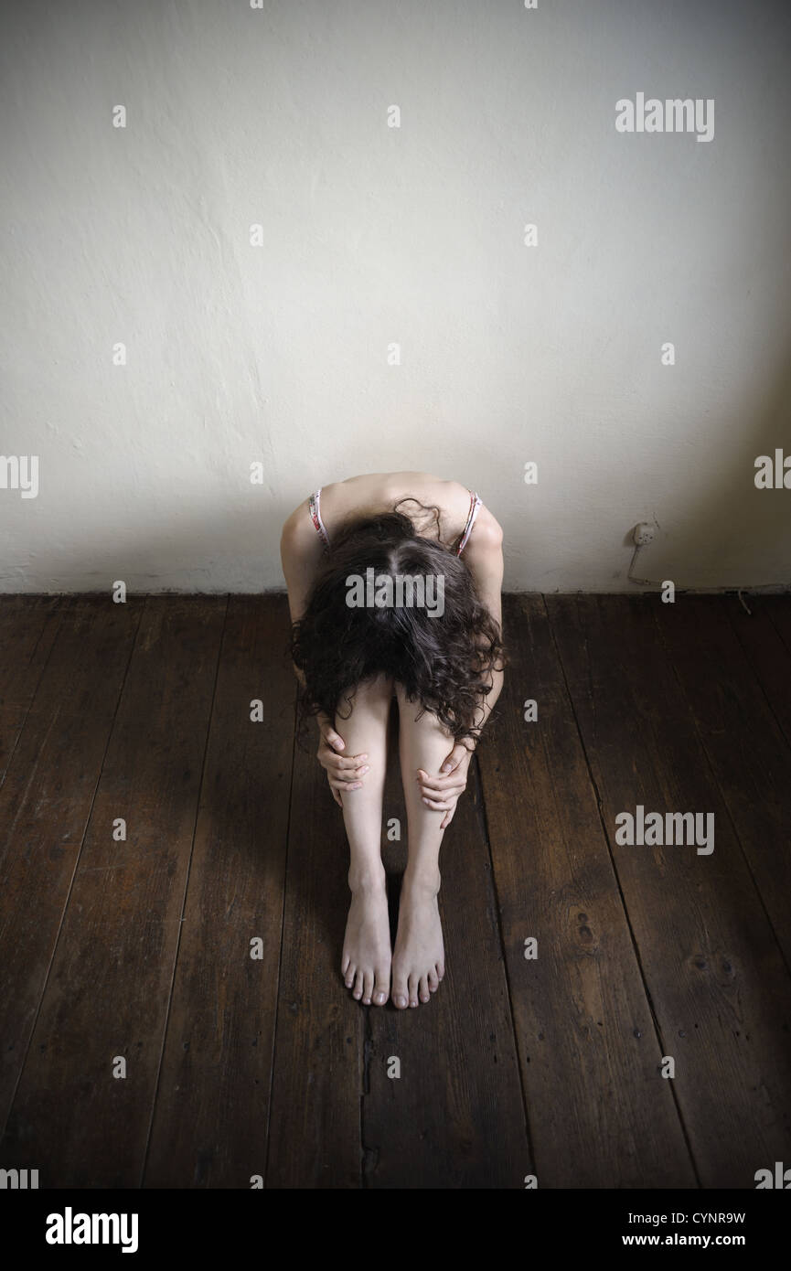a desperate young woman is sitting on an old wooden floor. top view - Stock Image