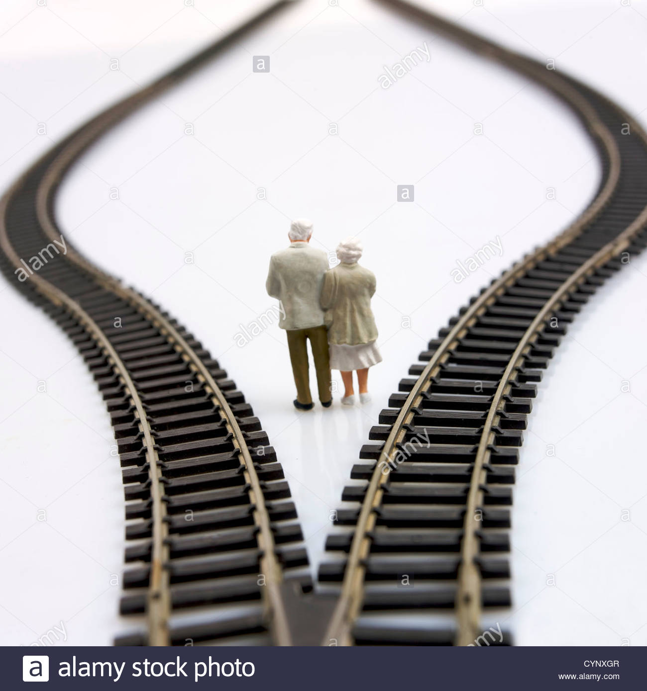 Model of elderly couple standing between two rail tracks - Stock Image
