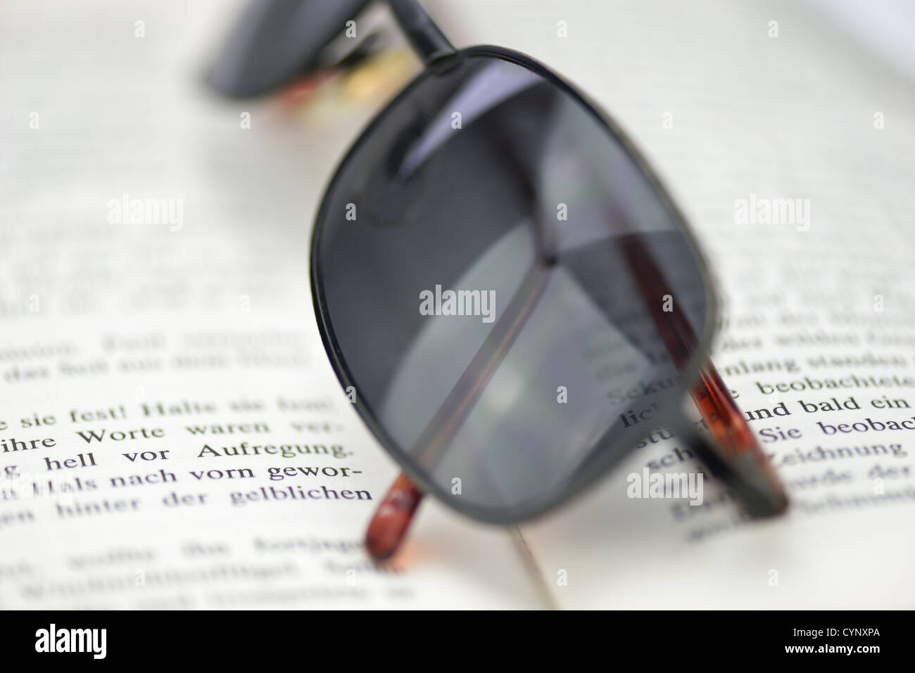 Tinted glasses on a book - Stock Image